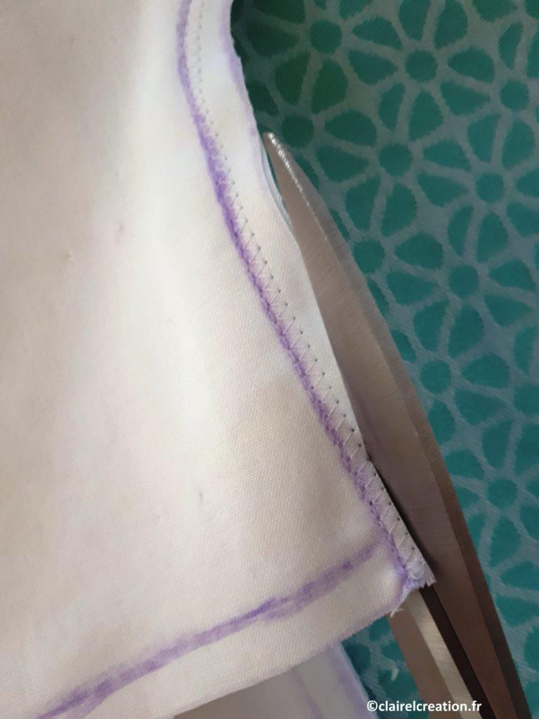 Coupe de l'excédent de tissu, au raz de la couture au point zigzag