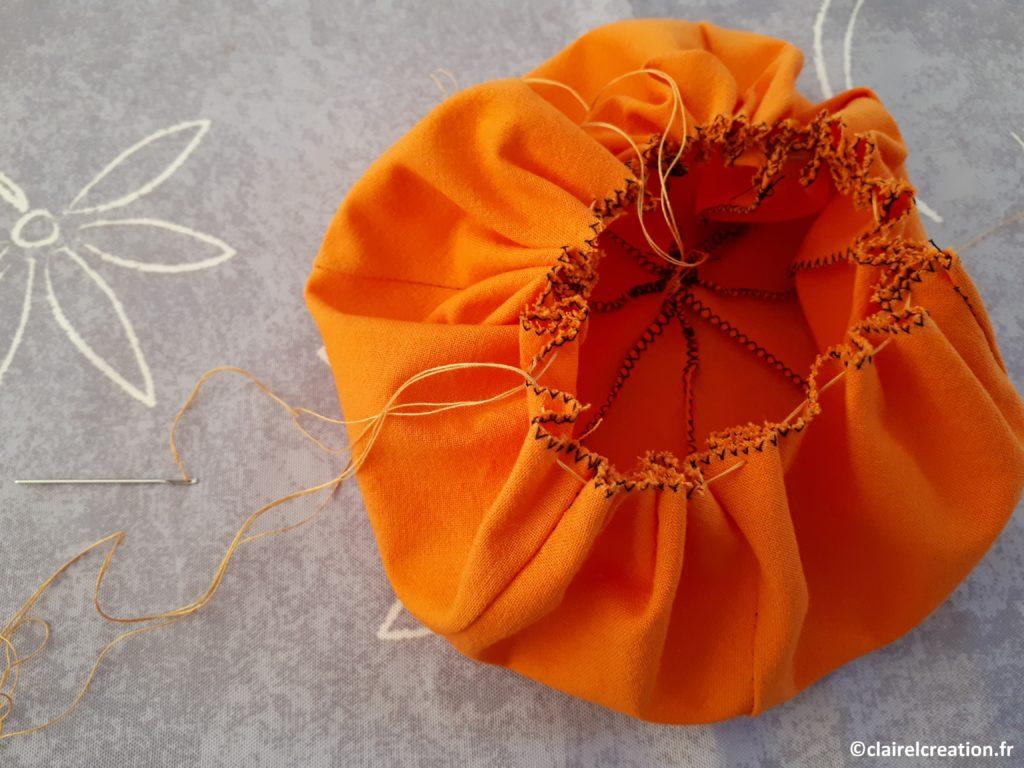 Tirer sur les fils du bord du cercle et attaché en laissant la place pour remplir avec la fibre (ouverture d'environ 2 cm de diamètre). Laisser une longueur de fil de 10 cm
